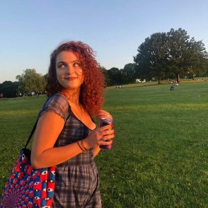 Ines is outside, in front of a green field and blue sky. She has curly red hair down to her shoulders. I nes is looking off to the left of the camera and smiling