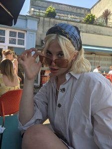 Jules is peering over the top of a pair of sunglasses. She is wearing a white button up shirt and a blue patterned bandana.