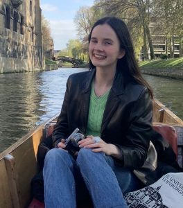 Nora is sat in a punting boat, on the river Cam, smiling at the camera.