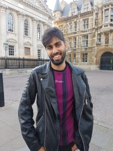 Mikha'el is stood in front of Kings College, cambridge. He is smiling at the camera