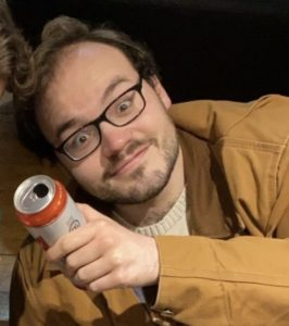 Sasha is looking up at the camera with a comical smile on his face. He is holding up a can of beer and wearing glasses