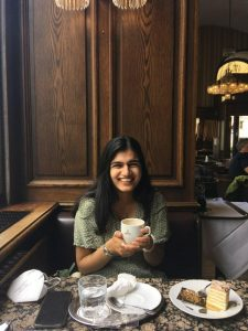 Picture of Umme, drinking tea in a cafe. She is wearing a green summer dress and smiling at the camera