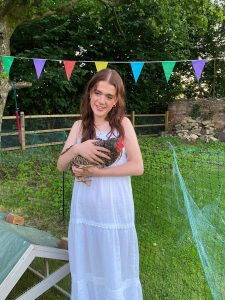 Phoebe is wearing a white maxi dress and holding a chicken called Mabel, standing in front of colourful bunting