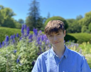 Harry is stood outside, in front of a lavender field. He is wearing a blue button up shirt, has short brown hair and is smiling towards the camera.